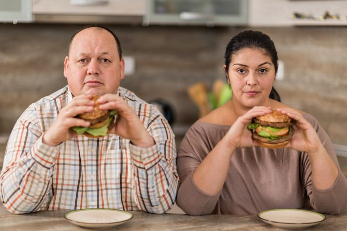 Coppia sovrappeso mangia hamburger