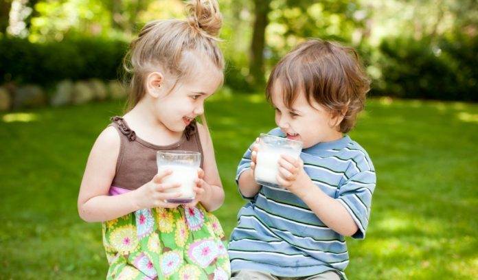 Due bambini bevono latte