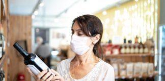 Donna con mascherina sceglie il vino al supermercato