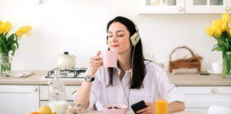 ragazza colazione beve tazza caffè ascolta musica