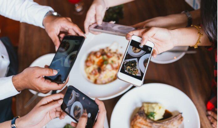 gruppo amici telefoni foto piatti cibo