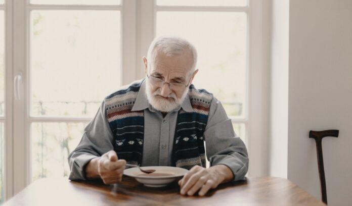 anziano seduto a tavola mangia minestra